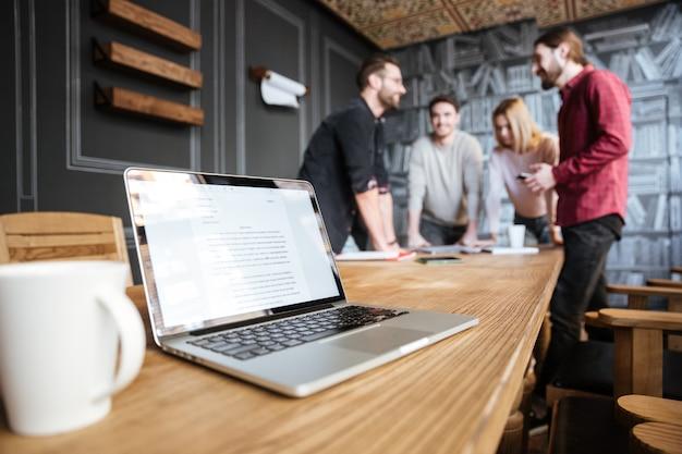 Imagen de jóvenes colegas atractivos de pie en la oficina y coworking