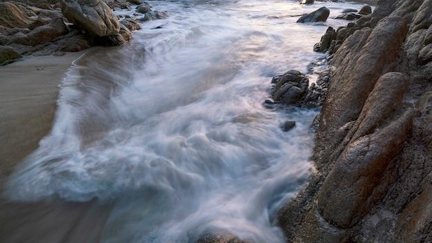 Imagen de larga exposición del paisaje marino de olas rompiendo con rocas