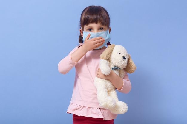 Imagen de linda chica europea en edad preescolar viste máscara médica y sostiene un juguete para perros en la mano, cubre la boca con la palma