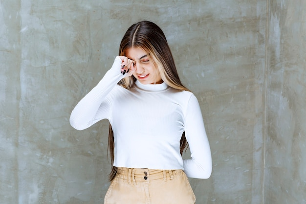 Imagen de una linda chica modelo de pie y posando contra la piedra