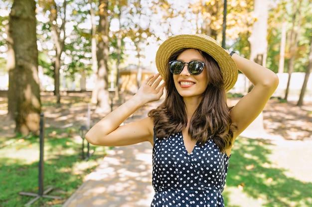 Imagen de linda mujer con cabello corto oscuro vestida con vestido está caminando en el parque con una sonrisa encantadora. lleva sombrero de verano y gafas de sol negras.