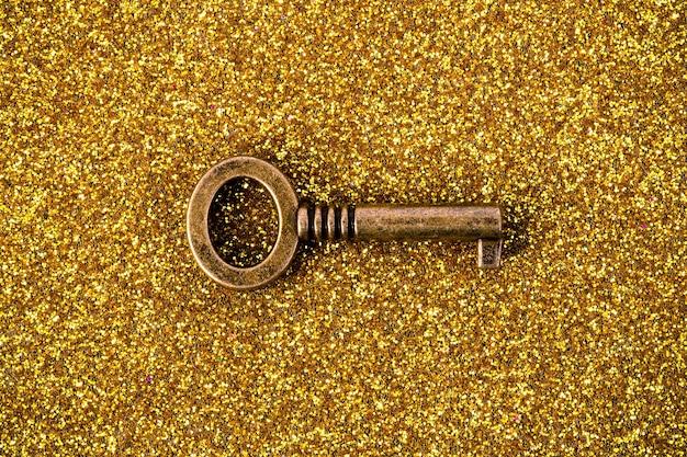 Imagen de llave de bronce sobre fondo dorado