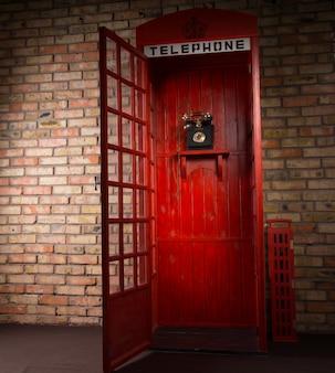 Imagen de longitud completa de la cabina telefónica pública roja con teléfono antiguo y puerta abierta