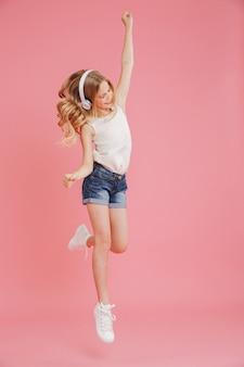 Imagen de longitud completa de una chica rubia de 8 a 10 años en ropa casual bailando y escuchando música con auriculares inalámbricos en la cabeza, aislada sobre fondo rosa