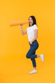 Imagen de longitud completa de la joven morena asiática llamando con boquilla aislado en amarillo