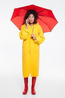 Imagen de longitud completa de mujer africana sorprendida en gabardina escondiéndose bajo el paraguas mientras habla por teléfono inteligente y mirando a la cámara sobre fondo blanco.