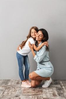 Imagen de longitud completa de mujer feliz con hija sonriendo y abrazándose juntos, aislado sobre gris