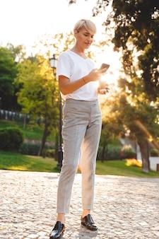 Imagen de longitud completa de una mujer rubia adulta con ropa casual sonriendo, mientras sostiene el teléfono móvil y el café para llevar durante la caminata en el parque verde de la ciudad