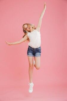 Imagen de longitud completa de la niña feliz 8-10 en ropa casual bailando y escuchando música con auriculares inalámbricos en la cabeza, aislada sobre fondo rosa