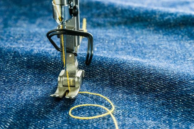 Imagen macra de las piezas de la máquina de coser de la siguiente manera aguja y pie prensatelas en tejido jean.