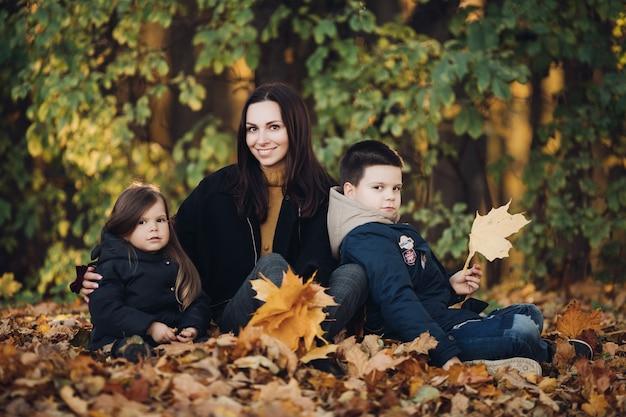 Imagen de mamá con largo cabello negro en abrigo negro, niño bonito con su hermana menor sostienen ramos de hojas de otoño