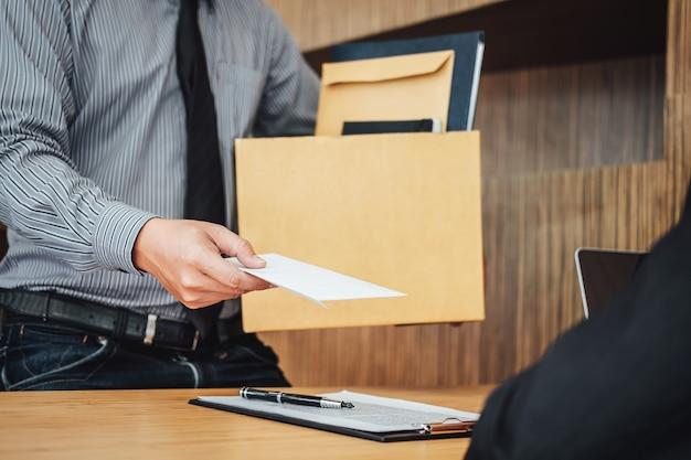 Imagen de la mano del empresario sosteniendo la caja de cartón y enviando una carta de renuncia