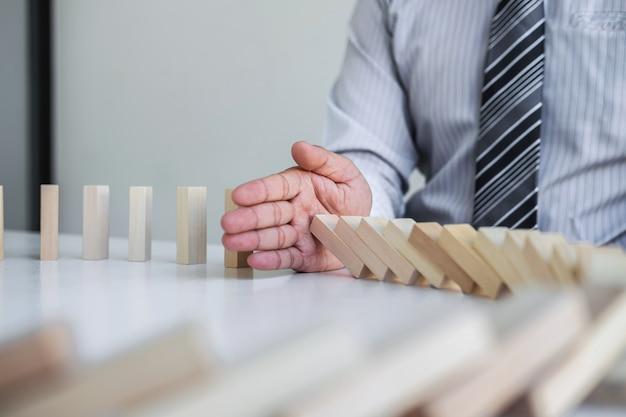 Imagen de la mano el hombre de negocios se detiene y protege contra el colapso del juego de bloques de madera que se está cayendo