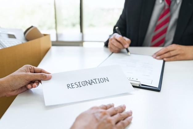 Imagen de la mano de una mujer de negocios enviando una carta de renuncia a su jefe
