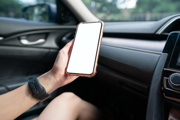 Imagen de la mano que sostiene el teléfono móvil con pantalla blanca de maqueta en el coche.