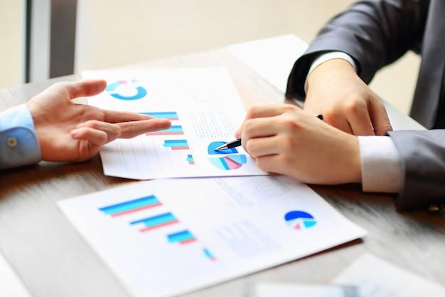 Imagen de manos humanas con bolígrafos apuntando al documento comercial en la reunión