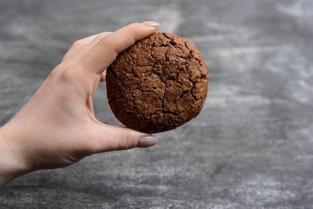 Imagen de manos sostienen galletas de chocolate