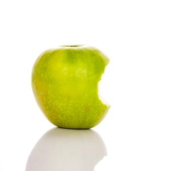Imagen de manzana verde mordida sobre un fondo blanco.