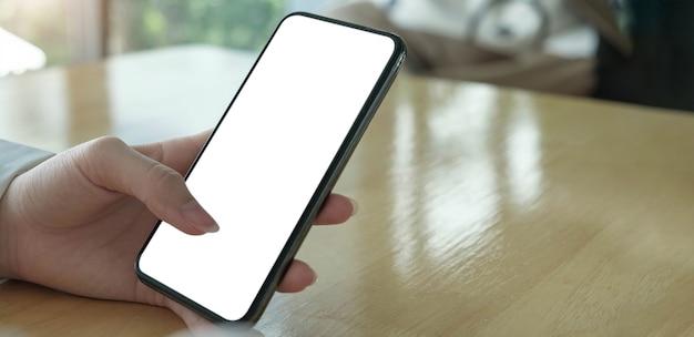 Imagen de maqueta en blanco teléfono celular con pantalla blanca. mano de mujer sosteniendo mensajes de texto usando el móvil en el escritorio en la oficina en casa.