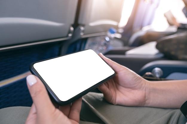 Imagen de la maqueta de la mano de la mujer sosteniendo un teléfono inteligente negro con pantalla de escritorio en blanco horizontalmente en la cabina
