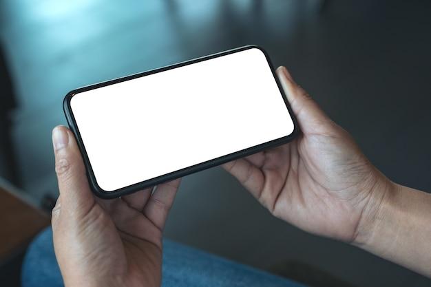 Imagen de maqueta de la mano de una mujer sosteniendo un teléfono móvil negro con pantalla de escritorio en blanco horizontalmente