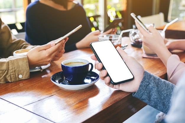 Imagen de maqueta de una mano sosteniendo y usando un teléfono móvil negro con pantalla de escritorio en blanco con amigos en la cafetería