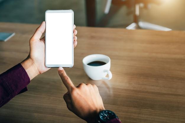 Imagen de la maqueta de las manos del hombre que sostienen el teléfono móvil blanco.