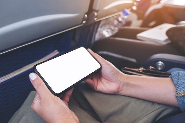 Imagen de maqueta de manos de mujer sosteniendo un teléfono inteligente negro con pantalla de escritorio en blanco horizontalmente en cabina