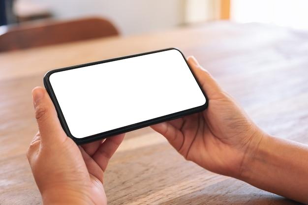 Imagen de maqueta de manos de mujer sosteniendo teléfono móvil negro con pantalla en blanco en blanco horizontalmente sobre mesa de madera