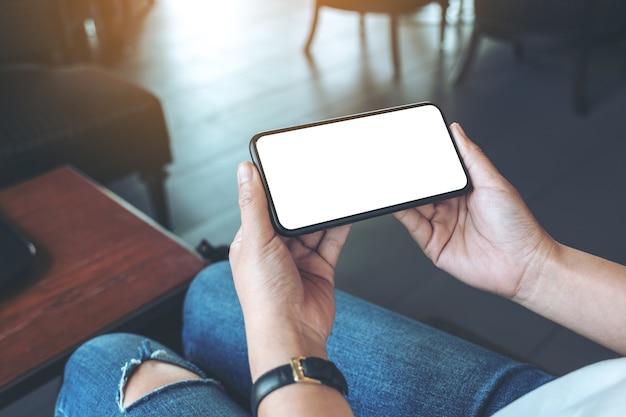 Imagen de maqueta de manos de mujer sosteniendo teléfono móvil negro con pantalla en blanco horizontalmente en café