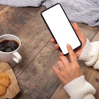 Imagen de la maqueta de las manos de la mujer sosteniendo un teléfono móvil negro con pantalla en blanco en la mesa de madera.