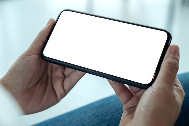 Imagen de maqueta de manos de mujer sosteniendo teléfono móvil negro con pantalla de escritorio en blanco horizontalmente