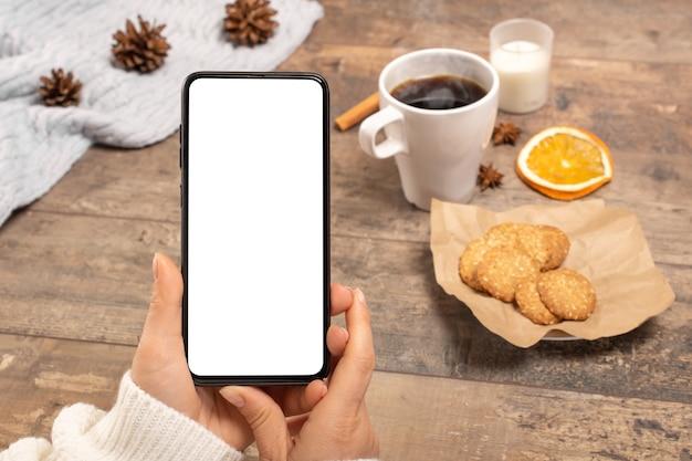 Imagen de maqueta de manos de mujer sosteniendo teléfono móvil con pantalla en blanco en la mesa de café.