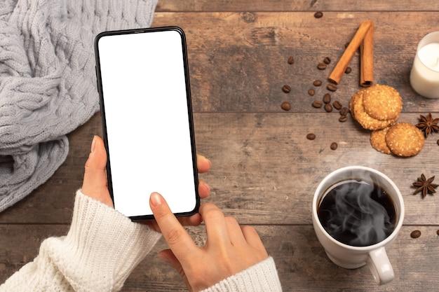 Imagen de maqueta de manos de mujer sosteniendo teléfono móvil con pantalla de escritorio en blanco mientras toma café en la cafetería.