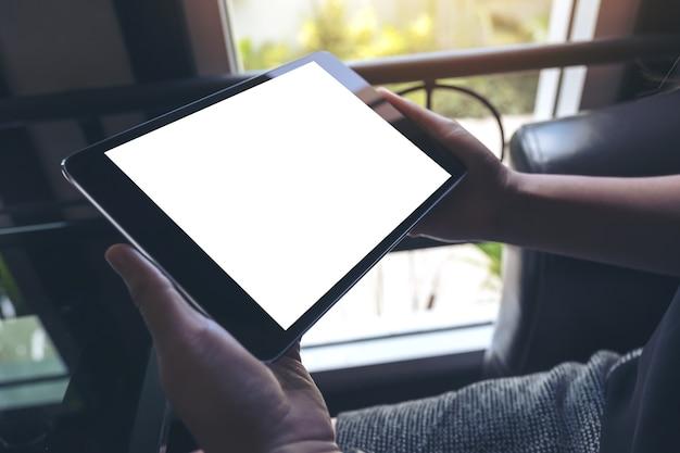 Imagen de maqueta de manos sosteniendo tablet pc negro con pantalla en blanco en blanco