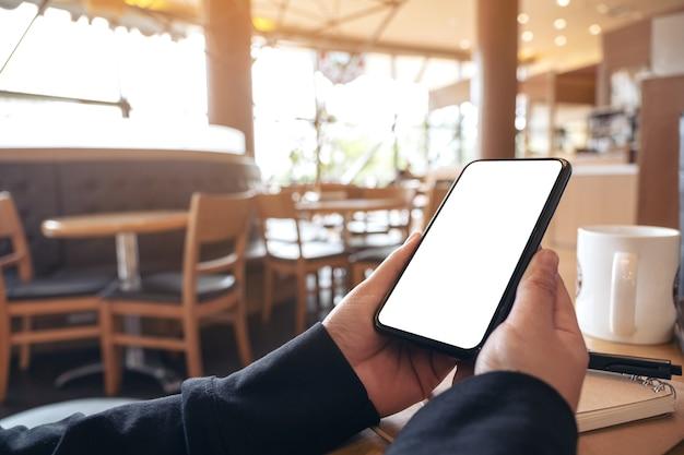 Imagen de maqueta de manos sosteniendo teléfono móvil negro con pantalla en blanco en café