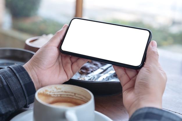 Imagen de maqueta de manos sosteniendo teléfono móvil negro con pantalla de escritorio en blanco horizontalmente con taza de café sobre la mesa