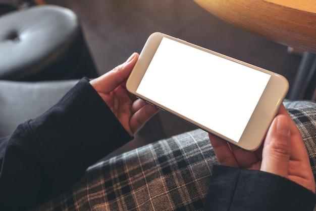 Imagen de maqueta de manos sosteniendo y usando un teléfono móvil blanco con pantalla en blanco horizontalmente mientras está sentado en la cafetería