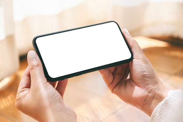 Imagen de maqueta de manos sosteniendo y usando un teléfono móvil negro con pantalla de escritorio en blanco horizontalmente