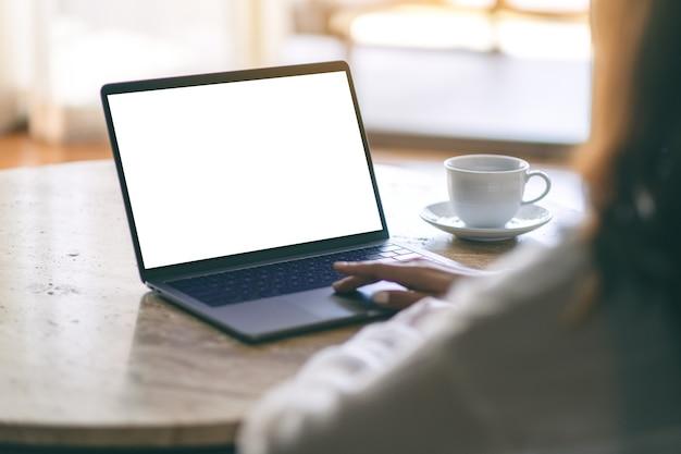 Imagen de maqueta de una mujer que usa y escribe en una computadora portátil con una pantalla de escritorio blanca en blanco sobre la mesa mientras está sentada en el piso de la casa