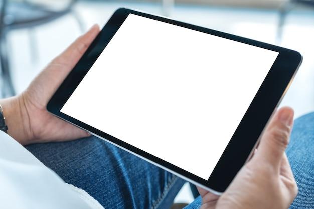Imagen de maqueta de una mujer sentada y sosteniendo una tablet pc negra con una pantalla de escritorio blanca en blanco horizontalmente