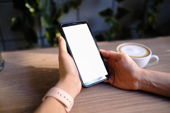 Imagen de maqueta de una mujer sosteniendo y mostrando teléfono móvil negro con pantalla en blanco en la cafetería.