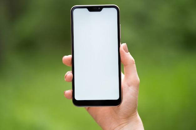 Imagen de la maqueta, teléfono celular de pantalla blanca en blanco. mano de hombre sosteniendo mensajes de texto usando el móvil en el escritorio en la cafetería