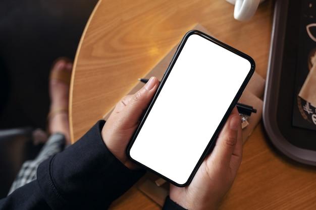 Imagen de maqueta de vista superior de manos sosteniendo teléfono móvil negro con pantalla en blanco en café vintage