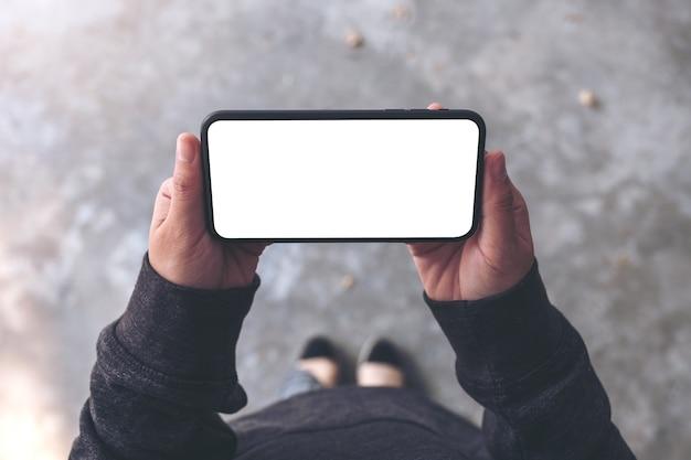 Imagen de maqueta de vista superior de una mujer sosteniendo un teléfono móvil negro con pantalla de escritorio en blanco horizontalmente mientras está de pie sobre un piso de concreto