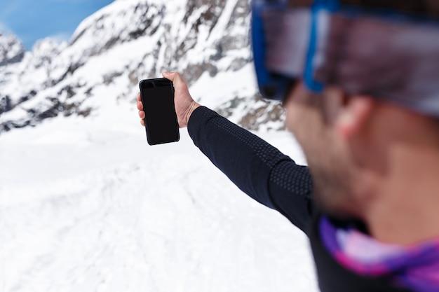 Imagen de marco de un snowboarder en ropa de deportes de invierno haciendo foto selfie con su teléfono móvil en las montañas nevadas
