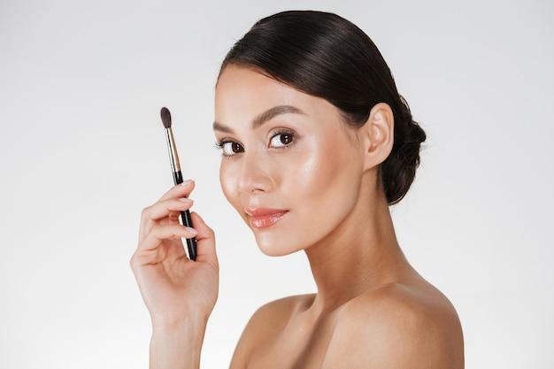 Imagen de media vuelta de mujer complacida con piel fresca mirando a la cámara y sosteniendo el pincel de maquillaje para sombra de ojos, aislado sobre la pared blanca