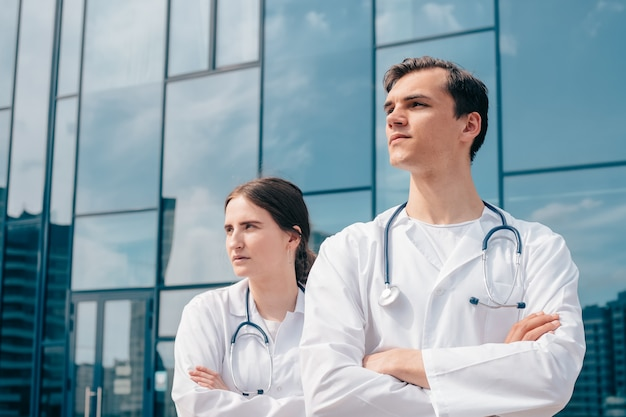 Imagen de médicos de pie frente al edificio del hospital.