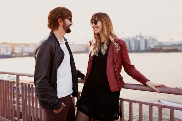Imagen de moda al aire libre de pareja elegante en traje casual, chaqueta de cuero y gafas de sol de pie en el puente. hombre guapo con barba con su novia pasando tiempo romántico juntos.