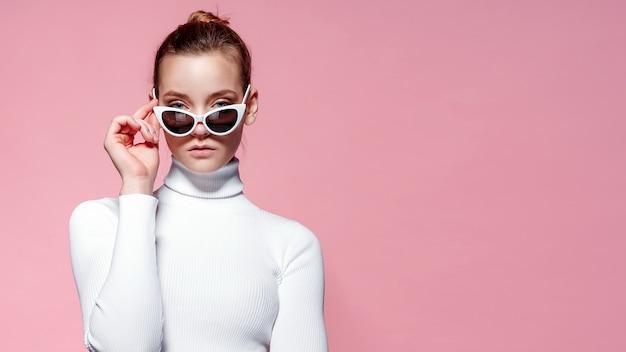 Imagen de moda de mujer elegante hermosa en golf de punto blanco y gafas de sol posando sobre pared rosa.